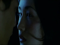 Maggie Q making out with a guy in the ocean and removing